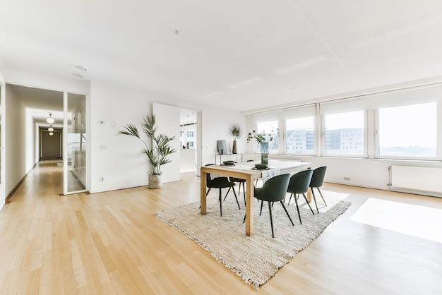 편안한 소파와 안락의자가있는 세련된 거실의 인테리어는 현대 아파트의 테이블 주위에 카펫에 쿠션이 놓여 있습니다.