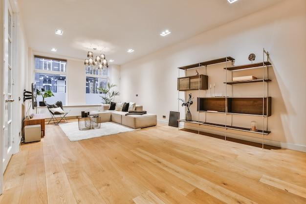 Интерьер стильной гостиной с удобным диваном и креслами с подушками на ковре вокруг стола в современной квартире