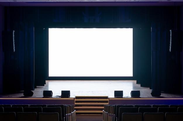 흰색 모니터가있는 무대의 극장 또는 영화관의 홀 내부
