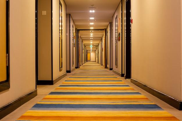 Интерьер отеля длинный коридор с полосатым переходом.