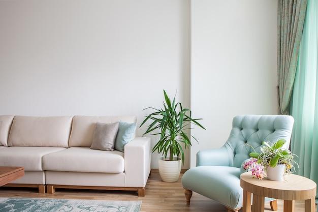 白いソファ、ミントの肘掛け椅子、植物で飾られた木製のコーヒーテーブル付きのリビングルームのインテリア。