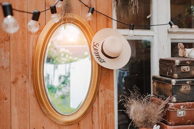 ヴィンテージ アクセサリーの家具を備えた、夏の国の居心地の良い木の素朴なテラスのインテリア。田舎の夏休みの雰囲気のある室内。環境にやさしい自然素材を無駄なく