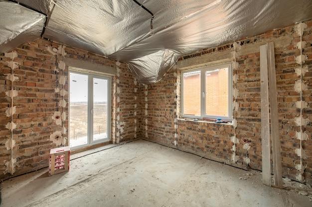 Интерьер недостроенного кирпичного дома с бетонным полом и голыми стенами, готовыми к оштукатуриванию в стадии строительства. развитие недвижимости