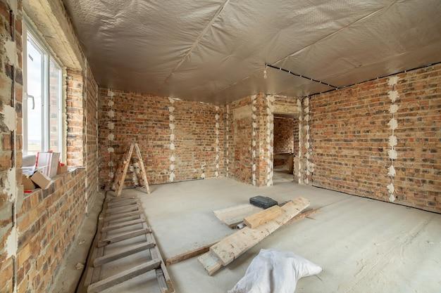 Интерьер недостроенного кирпичного дома с бетонным полом и голыми стенами, готовыми к штукатурке в стадии строительства.