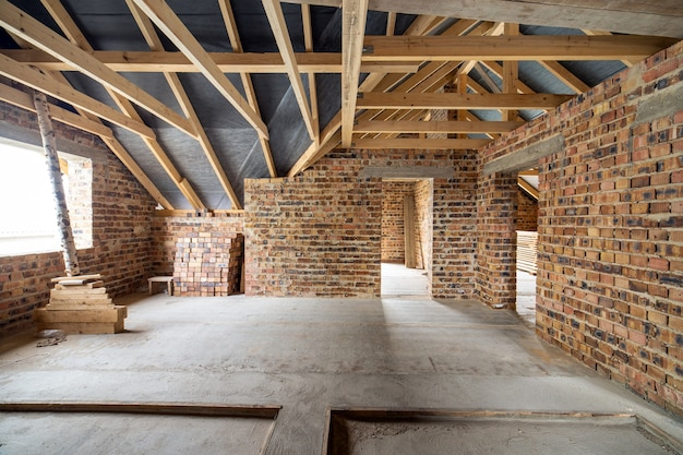 콘크리트 바닥이 있는 미완성 벽돌 집의 내부, 석고를 칠할 준비가 된 맨 벽, 건설 중인 목조 지붕 프레임 다락방.