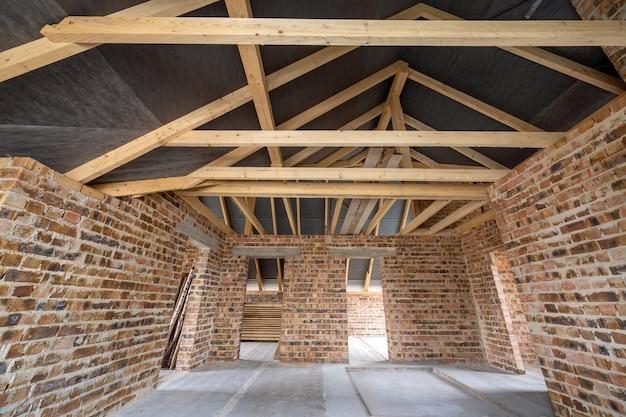 Интерьер незавершенного кирпичного дома с бетонным полом, голыми стенами, готовыми к штукатурке, и деревянным кровельным каркасом мансарды под строительство.