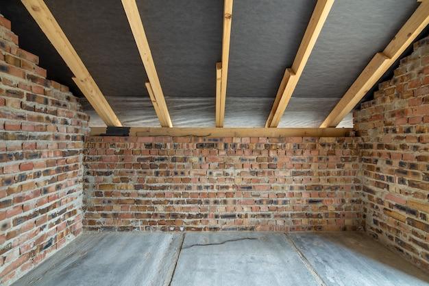 콘크리트 바닥이있는 미완성 벽돌 집의 내부, 석고 및 목재 루핑 준비가 된 맨 손으로 벽