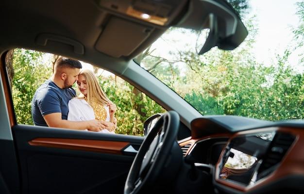 Интерьер автомобиля. пара, обнимая друг друга в лесу возле современного автомобиля.