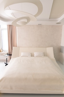Интерьер белой роскошной спальни с большой кроватью