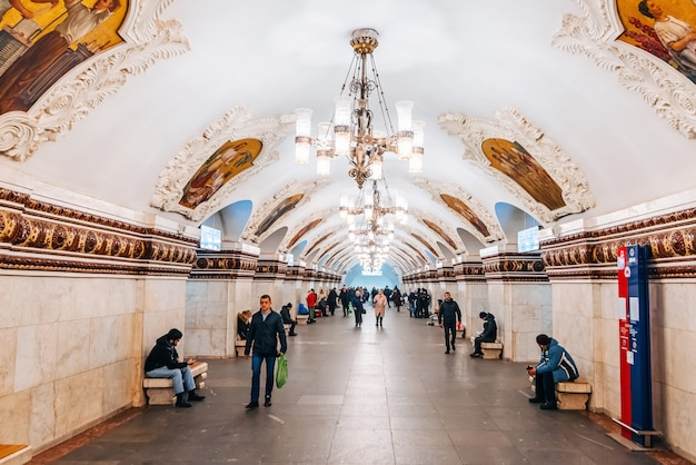 The interior of an old beautiful underground metro station in moscow and a crowd of people