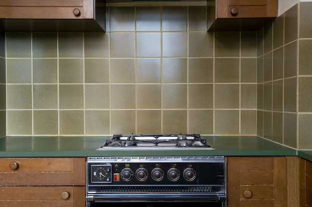 Interior of a old retro vintage kitchen with antique oven with brown wooden cabinets, green old school stylish tiles,needs renovation close to