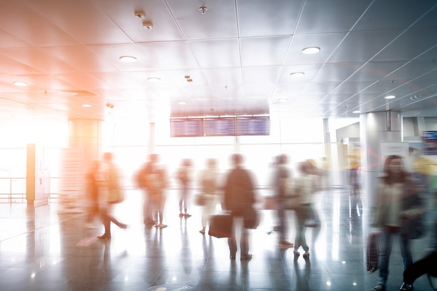 Interior photo of blurred passengers looking at airport schedule at sunny day