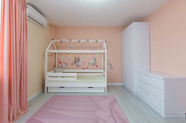 Interior photo children's room for a girl of light color with pink, with a white cot