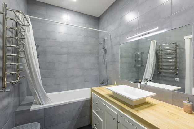 Interior photo of a modern bathroom with gray tiles in a small apartment