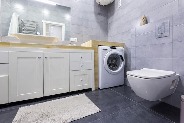 小さなアパートの灰色のタイルとモダンなバスルームのインテリア写真