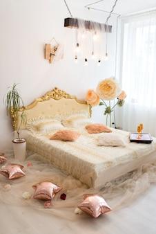 대형 침대와 아름다운 장식이있는 실내 사진 스튜디오