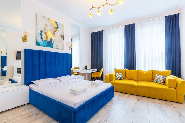 Interior photography, large bedroom in a modern loft style, with a double bed and a yellow sofa