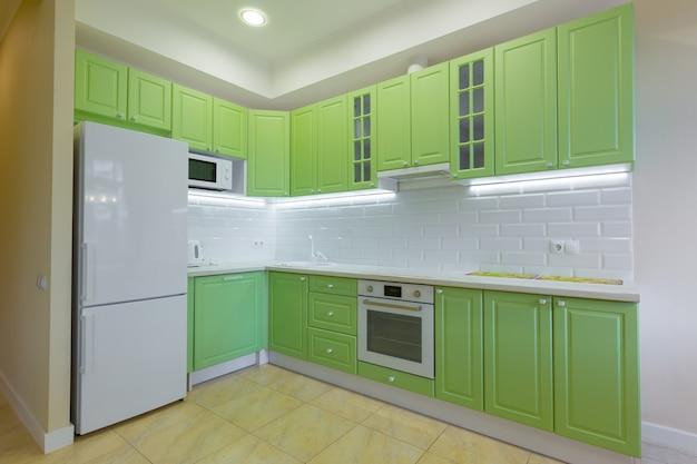 Интерьерная фотосъемка большой студийной комнаты с зеленой современной кухней