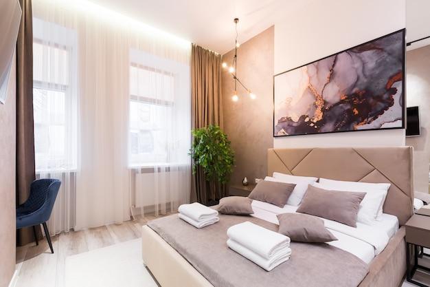 Интерьерная фотосъемка, современная спальня, с большой стильной кроватью, современный дизайн, в бежевом цвете.