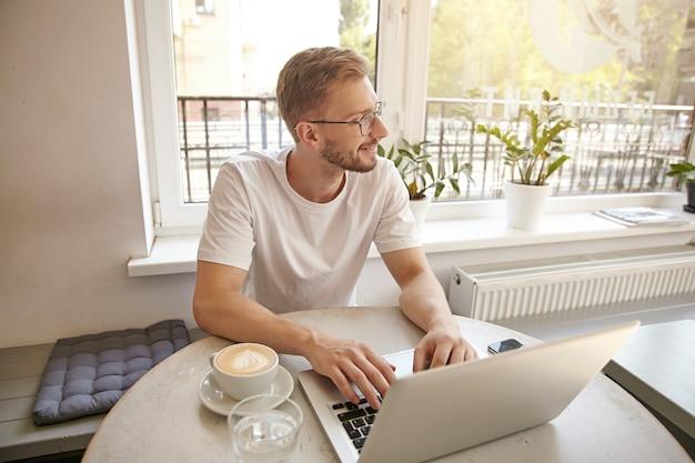 Ritratto interno del giovane maschio barbuto di bell'aspetto è seduto al tavolo con una tazza di caffè mentre si lavora al computer portatile, sorridente e guardando da parte sognante