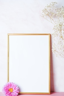 Interior poster mockup with a vertical gold metal frame with a white gypsophila branch and a pink fl...