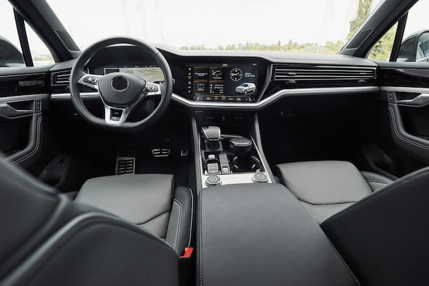 Interior of a prestigious modern black car. leather comfortable seats and accessories and steering wheel