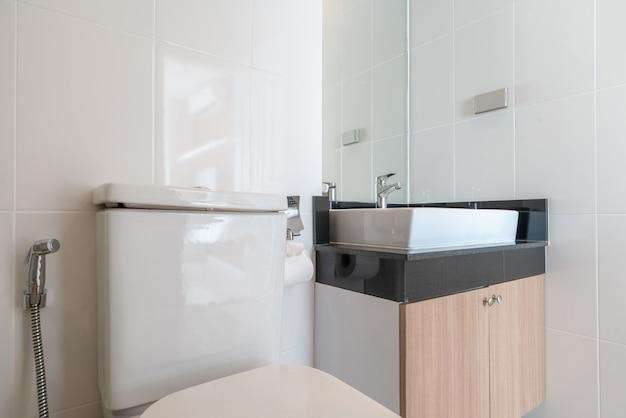 Interior real bathroom features basin, toilet bowl