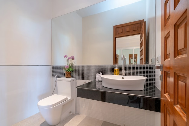 Interior real bathroom features basin, toilet bowl
