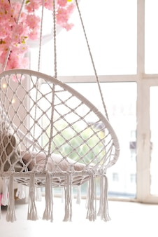 Interior of the room with white wicker swing hanging in front of large window