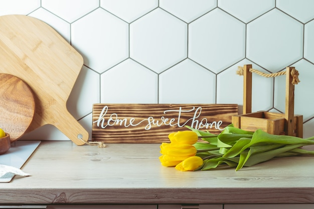 Interior shot. home sweet home handwritten sign on kitchen countertop next to yellow tulip bouquet and cutting boards on hexagonal white tile