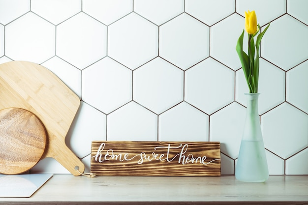 Interior shot. home sweet home handwritten sign on kitchen countertop next to yellow tulip in vase and cutting boards on hexagonal white tile background