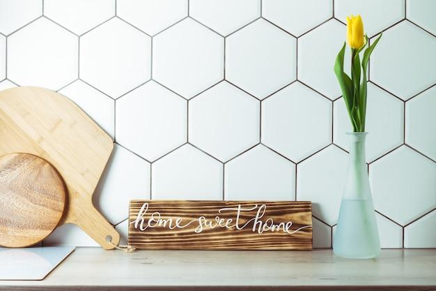インテリアショット。花瓶の黄色いチューリップと六角形の白いタイルの背景のまな板の横にあるキッチンカウンターの上のホームスイートホーム手書きサイン