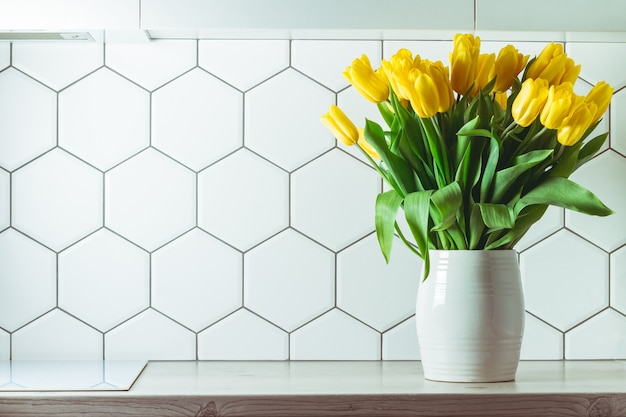 インテリアショット。六角形の白いタイルのキッチンカウンターに白い花瓶の黄色いチューリップの花束