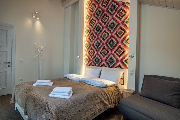 Interior of a spacious hotel bedroom with fresh linen on a big double bed. cozy contemporary room in a modern house.