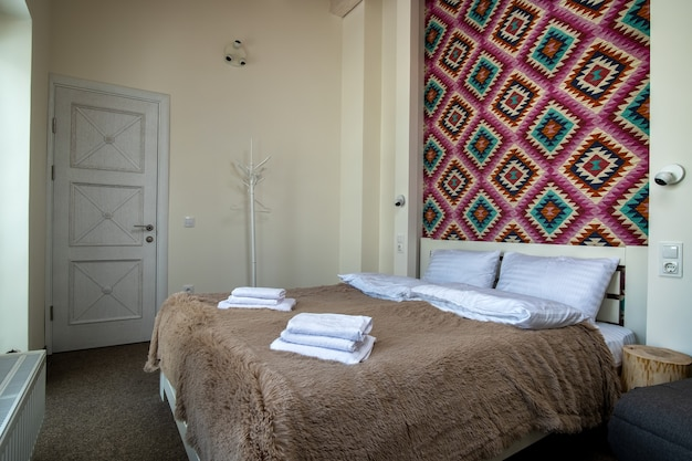 Interior of a spacious hotel bedroom with fresh linen on a big double bed
