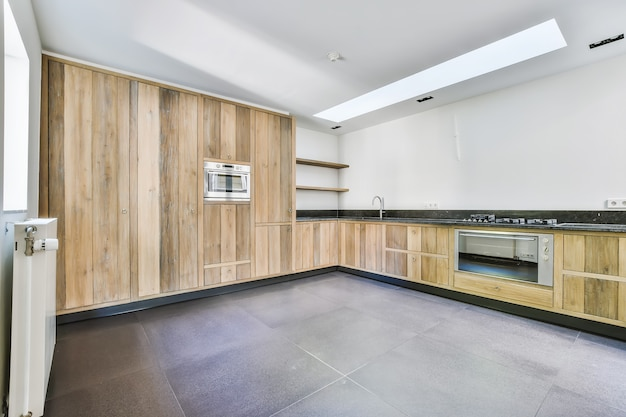 Interior of spacious kitchen with lumber furniture and modern appliances in new apartment