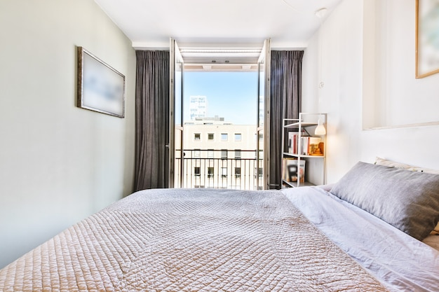 Interior of spacious light bedroom with balcony in contemporary apartment at sunny daytime