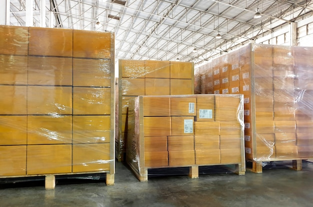 Interior of storage warehouse, stack package boxes on pallets in factory warehouse.