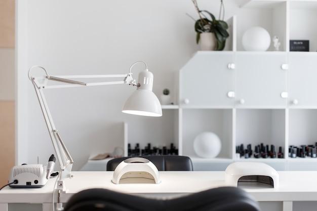 ネイルケアのためのインテリアスタジオ。ランプと道具を備えたマニキュア用の白い部屋
