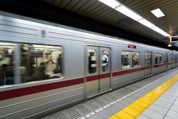 Interior of a tokyo subway station and platform with subway commuters in tokyo, japan.
