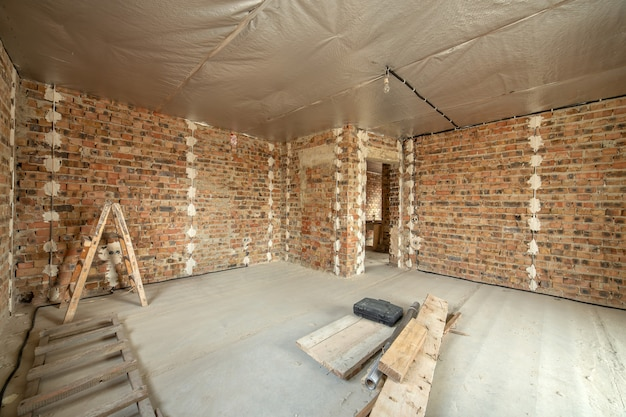 Interior of unfinished brick house with concrete floor and bare walls under construction.