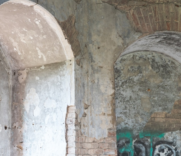 Interior view of an abandoned old building with an arch in the wall