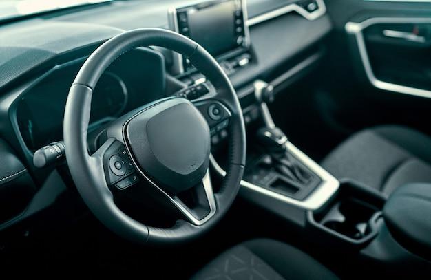 黒のサロンと車の内部ビュー。高級車のインテリア。ステアリングホイール、シフトレバー、ダッシュボード。