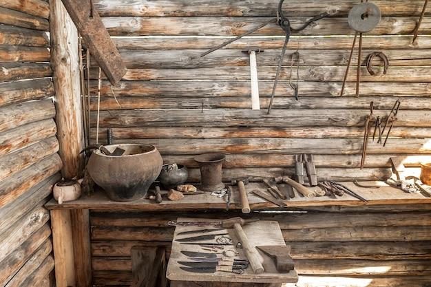 古い村の鍛造の内部ビュー鍛冶屋の道具は木製の作業台に横たわっています