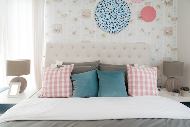 Interior of white bedroom with double bed and color pillows at home.