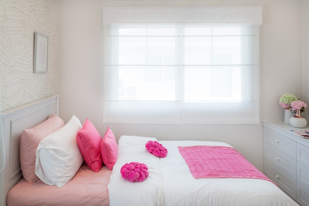 Interior of white bedroom with double bed and pink pillows and bookshelf at home.