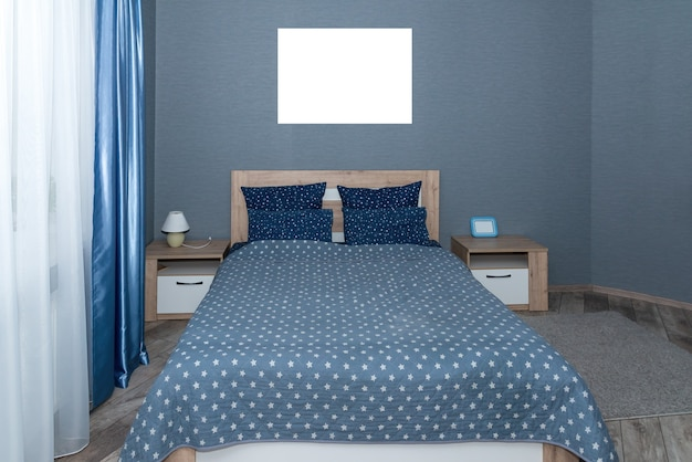 Interior with blue bed linen on the sofa. bedroom with bed, blue bedding, and bedside table. blue pillows, grey duvet case on bed with wooden headboard. front view.