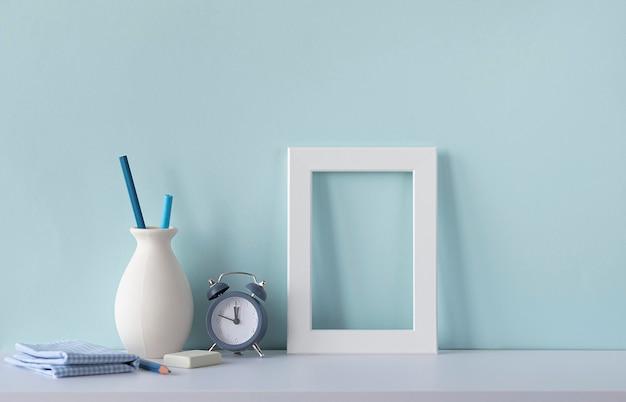 블루톤의 인테리어. 디자이너의 직장입니다. 책상, 알람 시계, 연필 꽃병에 흰색 나무 빈 프레임. 텍스트를 위한 장소가 있는 모형.