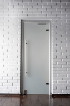 白いレンガの壁にすりガラスのドアのあるインテリア