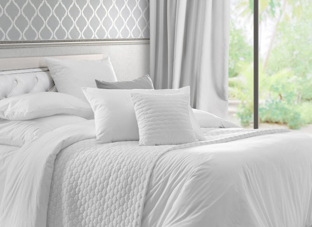 Интерьер с окном с видом на сад и белой кроватью.
